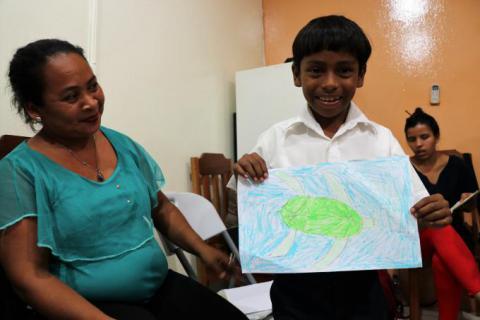 Isaí mostrando su dibujo junto a Claribel, su mamá.